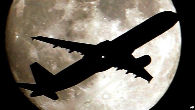 Un avión parece cruzar la luna al aproximarse al aeropuerto internacional de Los Angeles, en California.