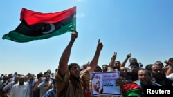 Men hold up a picture of slain lawyer and prominent Libyan activist Abdelsalam al-Mosmary, during his funeral in Benghazi, July 27, 2013.