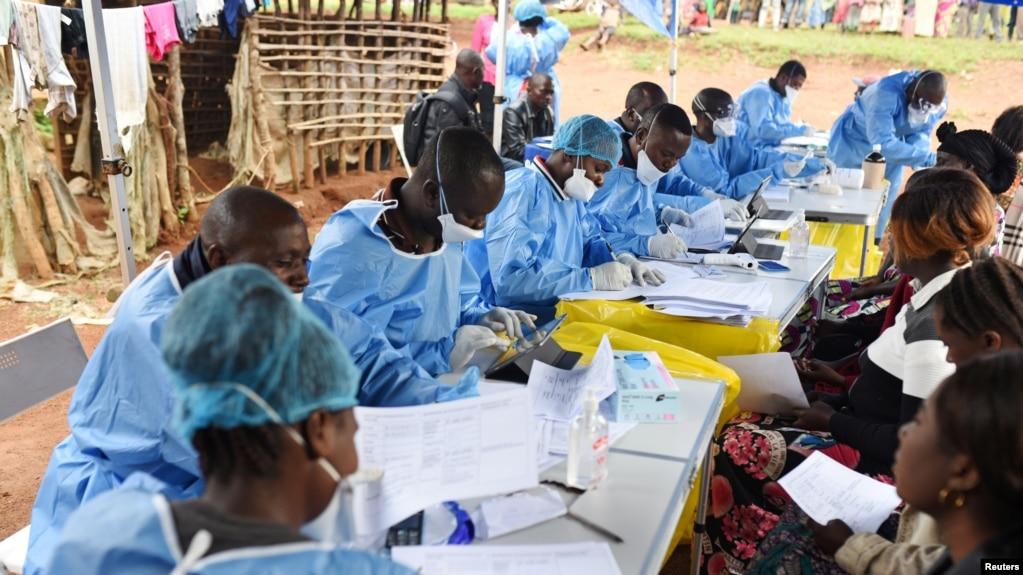 ARCHIVO - Trabajadores de salud congoleses inscriben a pacientes y les toman la temperatura antes de vacunarlos contra el ébola en la aldea de Mangina, provincia de Kivu, República Democrática del Congo. 18-8-18.