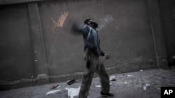 Chiến binh nổi dậy ném lựu đạn tự chế về phía binh sĩ chính phủ Syria tại thành phố Aleppo.