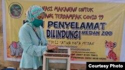 Seorang warga saat memberikan donasi koin peduli satwa-satwa di Kebun Binatang Medan. (Courtesy: Medan Zoo)