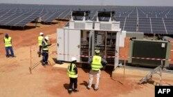Des techniciens sur un site de production d'énergie photovoltaïque à Bokhol, au Sénégal, le 22 octobre 2016. C'était l'un des plus grands projets d'énergie solaire d'Afrique subsaharienne. (Photo de SEYLLOU / AFP)