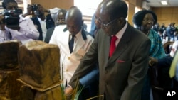 "Zimbabwe's President Robert Mugabe cuts his birthday cake as he marks his 93rd birthday at his offices in Harare, Tuesday, Feb. 21, 2017. Mugabe described his wife Grace, an increasingly political figure, as ""fireworks"" in an interview marking his 93rd bi"