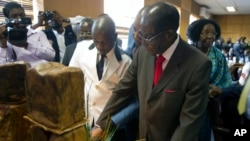 """Zimbabwe's President Robert Mugabe cuts his birthday cake as he marks his 93rd birthday at his offices in Harare, Tuesday, Feb. 21, 2017. Mugabe described his wife Grace, an increasingly political figure, as """"fireworks"""" in an interview marking his 93rd birthday."""