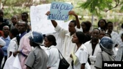 FILE - Zimbabwean riot police officers stand in front of doctors and nurses demonstrating over the deteriorating health system, outside Parirenyatwa public hospitals in Harare, Nov. 18, 2008.
