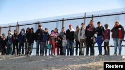 Um grupo de imigrantes centro-americanos rende-se à polícia de imigração na fronteira entre o México e os Estados Unidos. El Paso, Texas, 6 de Março, 2019.