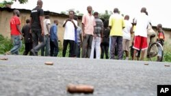 A man looks across at spent bullet casings lying on a street in the Nyakabiga neighborhood of Bujumbura, Burundi, Saturday, Dec. 12, 2015. Burundi's political violence continued Saturday as a number of people were found shot dead.