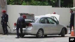 لاہور میں واقع امریکی قونصل خانے کے پاکستانی محافظ قونصل خانے میں داخل ہونے والی ایک گاڑی کی تلاشی لے رہے ہیں۔ (فائل فوٹو)