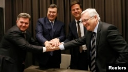Ukraine's Fuel Minister Stavitsky, Ukraine's President Yanukovich, Netherlands' Prime Minister Rutte and Voser CEO of Royal Dutch Shell shake hands after exchanging a signed agreement at WEF in Davos, January 24, 2013.