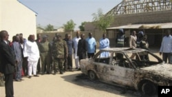 Bystanders gather around a burned car outside the Victory Baptist Church in Maiduguri, Nigeria, Saturday, Dec. 25, 2010