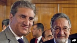 Pakistan's Foreign Minister Shah Mahmood Qureshi (L) poses with his Afghan counterpart Zalmai Rassoul before their meeting in Islamabad, Jan. 27, 2011.