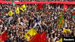 Demonstrators hold Kurdish flags and flags with portraits of the jailed Kurdistan Workers Party [PKK] leader Abdullah Ocalan during a gathering to celebrate Newroz in the southeastern Turkish city of Diyarbakir, March 21, 2013.