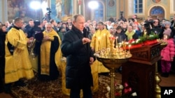 Russian President Vladimir Putin, center, attends midnight Orthodox Christmas Mass in a church in the village of Turginovo, about 150 kilometers (90 miles) northwest of Turginovo, Russia, late Wednesday, Jan. 6, 2016.