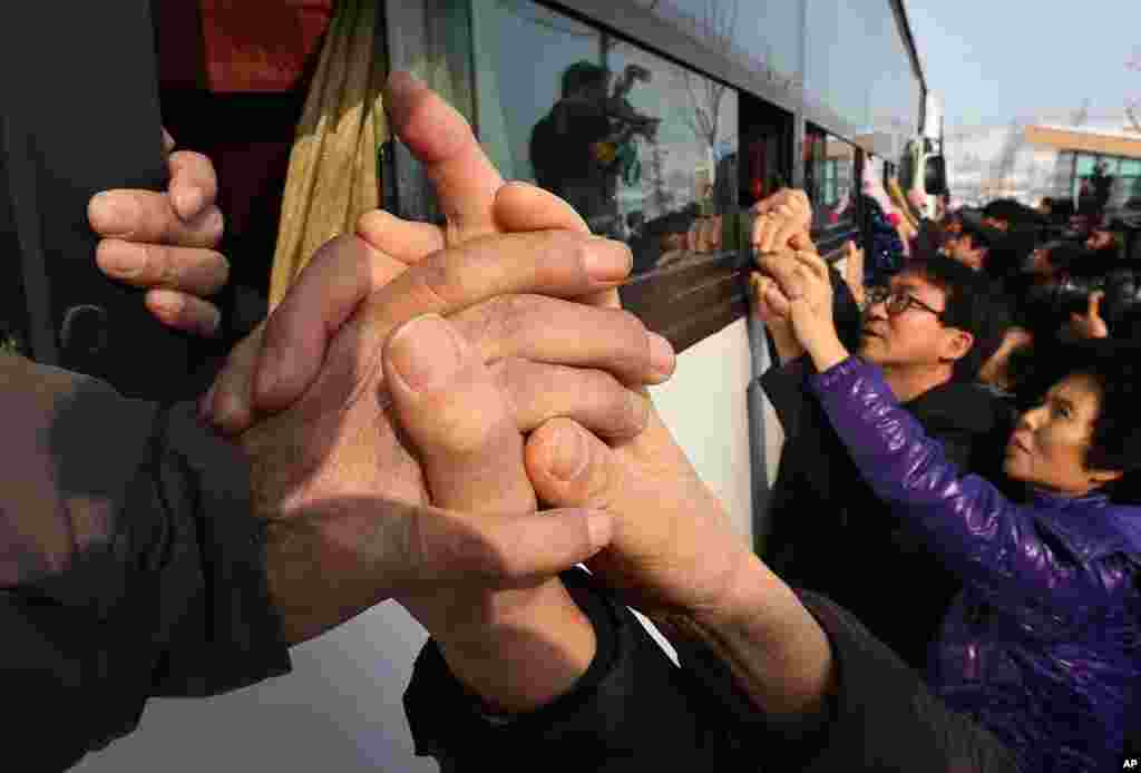 South Koreans hold their North Korean relative's hands on a bus after the Separated Family Reunion Meeting at Diamond Mountain in North Korea, Feb. 25, 2014. The first reunions of North and South Koreans in more than three years have been held in North Korea.