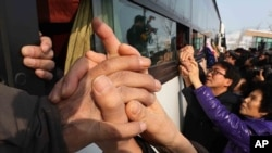 South Koreans hold their North Korean relative's hands on a bus after the Separated Family Reunion Meeting at Diamond Mountain in North Korea, Feb. 25, 2014
