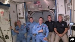 This photo provided by NASA shows Bob Behnken and Doug Hurley, far right, joining the the crew at the International Space Station, after the SpaceX Dragon capsule pulled up to the station and docked May 31, 2020.