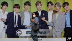A woman wearing a face mask to help protect against the spread of the coronavirus walks by a board showing members of South Korean K-Pop group BTS to advertise a local bank's money exchange in Seoul, South Korea, Wednesday, Sept. 30, 2020. (AP Photo…