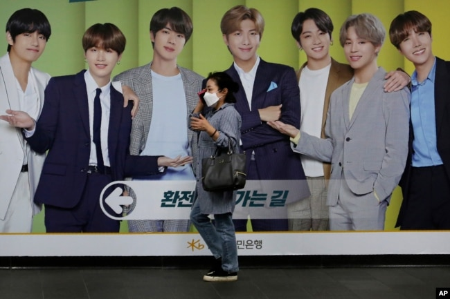 A woman wearing a face mask to help protect against the spread of the coronavirus walks by a board showing members of South Korean K-Pop group BTS in Seoul, South Korea, Wednesday, Sept. 30, 2020. (AP Photo)
