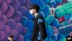 A pedestrian wears a face mask as he walks past a mural of a fish while strolling on the boardwalk at Coney Island, April 2, 2020, in the Brooklyn borough of New York.
