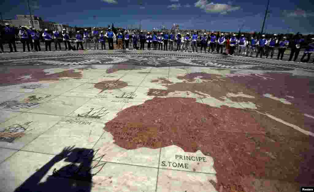 A group of volunteers gather on a square decorated with a giant world map during Earth Day celebrations in Lisbon, Portugal, April 22, 2015.