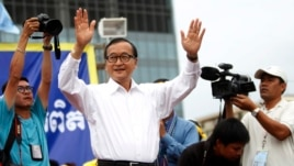Sam Rainsy, president of the Cambodia National Rescue Party (CNRP), greets his supporters in Freedom Park, Sept. 17, 2013.