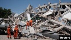Tim SAR mencari korban di antara reruntuhan bangunan hotel Roa Roa di Palu, Sulawesi Tengah, Senin (1/10).
