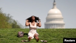 With the U.S. Capitol in the background, Kellye Sims flips her hair up as she basks in the sun, at the National Mall, during a record-setting heat wave in Washington, D.C., U.S., May 3, 2018. REUTERS/Kevin Lamarque TPX IMAGES OF THE DAY - RC147EA5A330