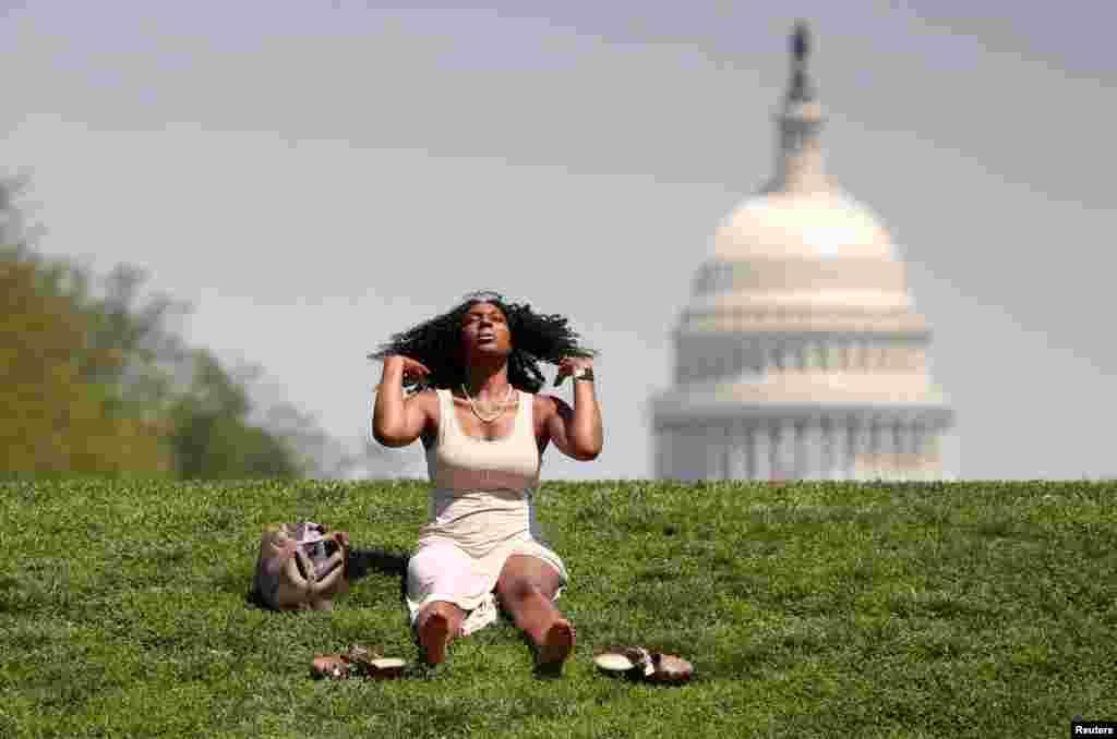 미국 워싱턴 DC의 내셔널몰에서 여성이 풀밭에 앉아 햇볕을 쬐고 있다.