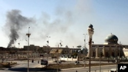 A plum of smoke is seen following a wave of attacks prior to the storming a police compound in the western Iraqi city of Ramadi, January 15, 2012.