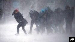 Warga di kota Boston kesulitan berjalan akibat tiupan angin kencang saat badai salju, Selasa (14/3).