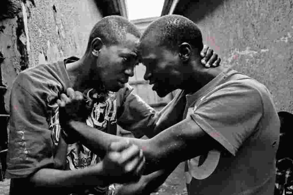 Vansing (left), age 20, fights with his friend Belusi, age 19, because he caught Belusi stealing from him, Giporoso, Kigali, Rwanda. Fri, Nov. 15, 2013. (Hamada Elrasam for VOA)