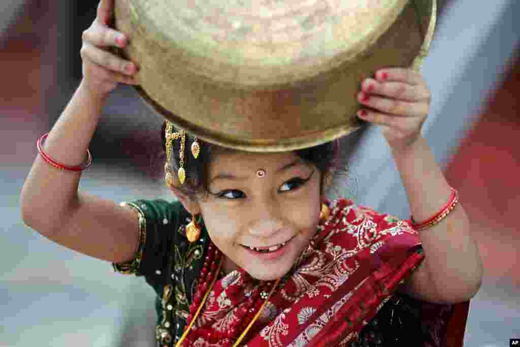 A young girl wearing traditional attire plays with a vessel while waiting for the Kumari puja to start at Hanuman Dhoka temple, in Kathmandu, Nepal.
