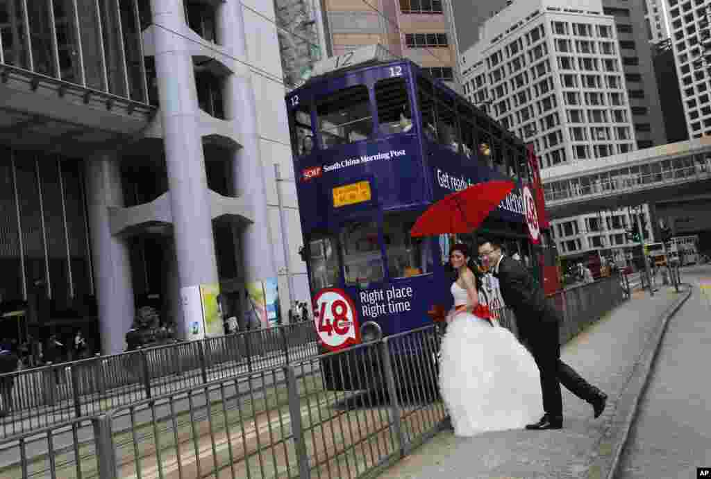 A couple poses for their wedding pictures next to a tram in downtown Hong Kong.