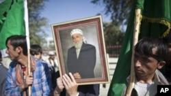 阿富汗前总统拉巴尼的支持者举着拉巴尼的照片聚集在他家外面