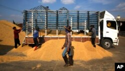 FILE - Workers unload rice from a truck at a rice collection center in the northeastern province of Roi Et , Thailand, Dec. 4, 2013. The military government has plans to spend over $900 million to boost the country's northeastern economy as it recovers from a two-year recession.