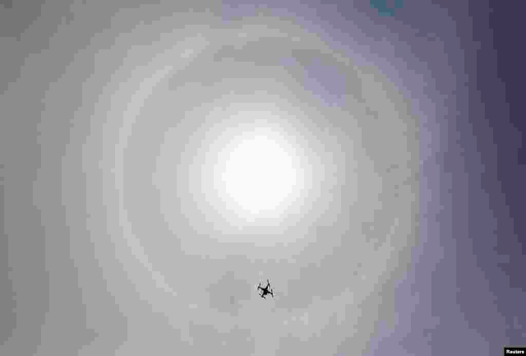 A drone flies in the sky as a solar halo is observed in Lima, March 5, 2014. The optical phenomenon is caused by refraction of sunlight through ice crystals in high clouds.