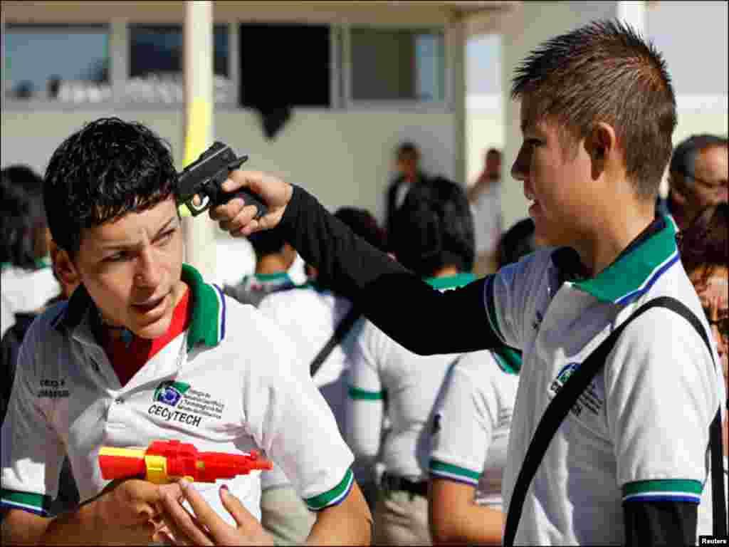 میکسیکو میں تشدد کیخلاف مہم کے دوران اسکول کے دو طالبعلم پستولوں سے کھیل رہے ہیں۔