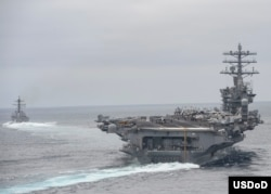 FILE - Ships assigned to the Nimitz Carrier Strike Group participate in a strait transit exercise in the Pacific Ocean in this April 3, 2017 photo.
