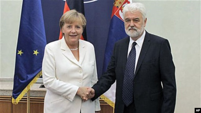 German Chancellor Angela Merkel (L) shakes hands with Mirko Cvetkovic, the Serbian Prime Minister, during an official visit, in Belgrade, Serbia, August 23, 2011