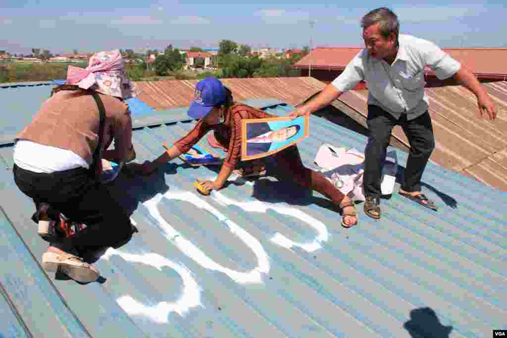 People in Tropeang Lavear display SOS messages on their roofs, which lies in the flight path to Phnom Penh international airport, Cambodia, November 13, 2014. (Nov Povleakhena/VOA Khmer)