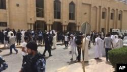 Pasukan keamanan dan jamaah berkumpul di luar masjid pasca pemboman masjid Imam Sadiq di Kuwait City, hari Jumat (26/6).