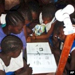 Girls in Sierra Leone read by the light of a single watt LED
