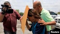 ہلاک ہونے والے تارک وطن رمیرز کی ایلیہ تانیہ شوہر کی نعشیں دیکھنے کے لیے سرد خانے جا رہی ہیں۔