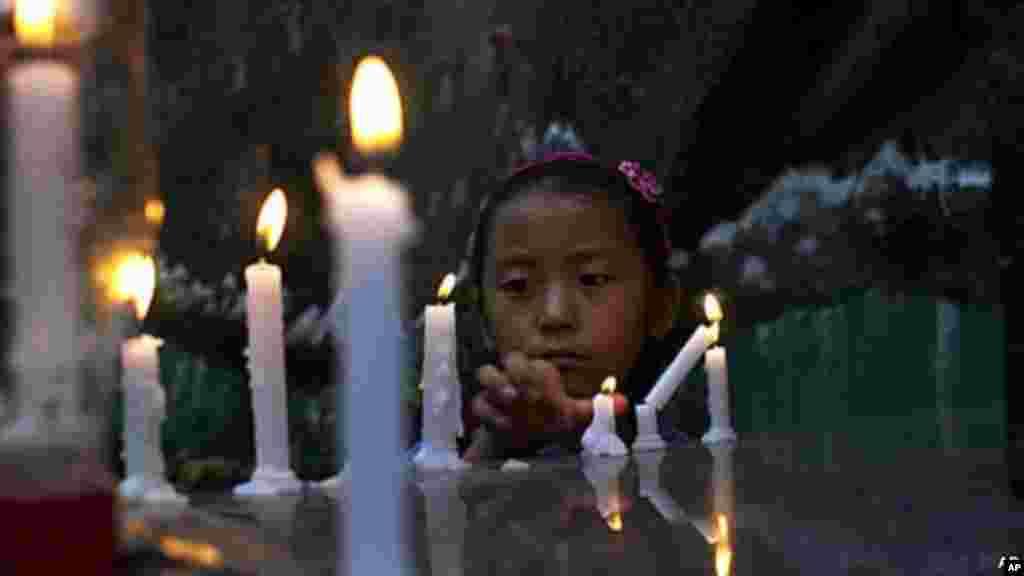 중국 간쑤성에서 분신 자살한 티베트 여성을 애도하기 위해 촛불을 밝히고 있는 한 티베트 소녀