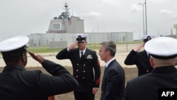 NATO Secretary-General Jens Stoltenberg (C) reviews an honor guard during an inauguration ceremony of the U.S. anti-missile station Aegis Ashore Romania (in the background) at the military base in Deveselu, Romania, May 12, 2016.