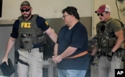 FBI agents escort businessman Fernando Scherrer-Caillet who was arrested in San Juan, Puerto Rico, July 10, 2019.