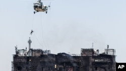 A rescue worker gets on a roof of an apartment building after a fire in Baku, Azerbaijan, Tuesday, May 19, 2015.