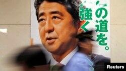 일본 도쿄에서 아베 신조 일본 총리 얼굴이 그려진 참의원 선거 홍보 벽보 앞으로 시민들이 지나고 있다.