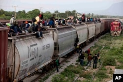 FILE - Central American migrants ride a freight train during their journey toward the U.S.-Mexico border in Ixtepec, Mexico, July 12, 2014. The migrants pay thousands of dollars per person for the illegal journey across thousands of miles in the care of smuggling networks that in turn pay off government officials, gangs operating on trains and drug cartels controlling the routes north.