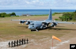 FILE - Philippine troops march as a Philippine Air Force C-130 transport plane carrying Philippine Defense Secretary Delfin Lorenzana, Armed Forces Chief Gen. Eduardo Ano and other officials, sits on the tarmac at the Philippine-claimed Thitu Island.